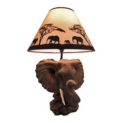 Zeckos - `Safari Light` Elephant Head Table Lamp w/ Silhouette Shade - This beautiful lamp features the head of an African Elephant atop a rock base. It measures 19 inches tall, the shade is 12 3/4 inches in diameter, and the cold cast resin base is 10 3/4 inches long by 7 1/2 inches wide. This piece is wonderfully detailed, from the wrinkles on the elephant`s skin to the gloss on his tiny eyes. The black 4 1/2 foot power cord has a thumbwheel on/off switch, and the lamp uses a 45 watt (max) type `A` bulb (included). It bcomes with a 12 3/4 inch diameter lampshade featuring a silhouette of a elephants traveling across the savanna