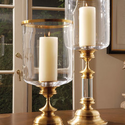 Estate Hurricane - Antique Brass - A piece of impressive gravitas, the Estate Hurricane in Antique Brass brings grandeur inspired by vintage stemware to the overscale, perfectly-detailed form of a hurricane lantern.  Pair with nautical or vintage accents for a story-rich appearance, or stand with greenery or flowers so their organic lines emphasize the turned details of the polished brass base.