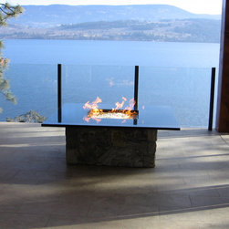 Outdoor Custom - This stylish propane fire pit was custom made By Okanagan Fireplace Den Ltd. It has 90,000btu's and is a conversation piece in itself. The black granite top reflects the flame.