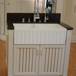 Mitrani Double Bowl Apron Sink - The Mitrani Double Bowl Apron Sink is dual function at its best. Not only does it combine two sinks in one but it is reversible as well. With one side fluted and the other smooth you can experiment with the style that fits your home best before installing the sink. This sink is made of Mitrani Titan Quartz, a mineral composite, which makes it great for a kitchen that is heavily used. It's extremely hard and scratch, stain and heat resistant. The sink is available in white and biscuit finishes. This large, contemporary sink will be the highlight of your kitchen for years to come!