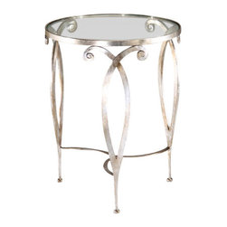 "Inviting Home - Round Glass Top Table (silver finish) - Round hand-wrought iron table with scroll design antiqued silverleaf finish and 3/8"" glass top 28-1/2"" x 23-3/4""H hand-crafted in Italy Round hand-wrought iron occasional table with scroll design. Wrought iron table finished in distressed antique silver-leaf and has 3/8"" thick glass top. This hand-wrought iron table is hand-crafted in Italy."