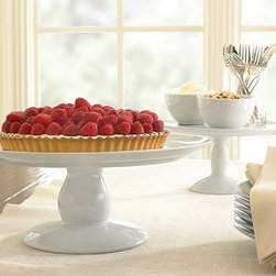 """Great White Cake Stand, Large - The products of great baking deserve a proper pedestal. This porcelain platform keeps baked goods on clear display above the rest of the table. Medium: 10"""" diameter, 5"""" high Large: 12"""" diameter, 6"""" high Rendered in high-fired, highly durable porcelain with a pure-white glaze. Generous round serving surface is supported by a broad round stem. Complements our PB White Dinnerware Collection or can be paired with antique china. Microwave and dishwasher safe."""