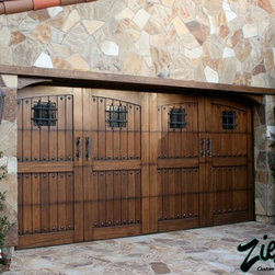 Tuscan Garage Doors - The region of Tuscany has great history and is known for its true artisans who create masterpieces out of the lands natural terrain. Most homes there are built by stone; but, it's the wood accents, doors, gates, and shutters that make their homes feel warm. Ziegler Tuscan Style Garage Doors capture the essence of the Italian countryside. Each garage door is designed to replicate an old cellar or stable door. We combine rustic woods and bold colors with hand forged distressed hardware to create the Ultimate Tuscan Garage Doors.