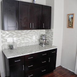 Customer Testimonial-  Mocha Shaker Cabinets - Finished Mocha Shaker kitchen with tile backsplash, lots of light from the skylight, and a  modern look with the bar pulls and tile choice
