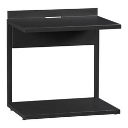 Bowery Nightstand - C-shaped metal frame outlines minimalist nightstand in low-sheen dark charcoal. Gallery top shelf has a slim cutout to tuck lamp and charging station cords. Open bottom shelf offers roomy storage for reading matter or d�cor. Part of the Bowery bed collection, nightstand can be positioned so that bed drawers open freely.