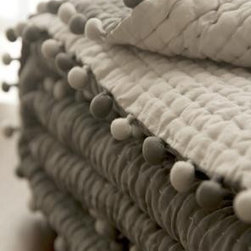 Ash Silk Pompom Quilt - Here's one pom-pom blanket that you might be able to sneak past your guy. It's nice to see pom-poms in a quieter design. The neutral shades of gray give this blanket a modern style.