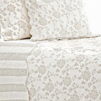 Monique Platinum Quilt - A dainty variation on a pale, lacy floral, the Monique Platinum Quilt uses the colors of ancestral silver to convey its message of antique grace.  An unabashed tribute to vintage fabric patterns and luxe old-world techniques, this upscale rose-patterned coverlet is quilted to emphasize the ruffled, charismatic petals of its flower motifs joined by lace-like swoops of stitching within scalloped borders.