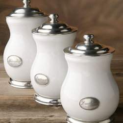 "Arte Italica Tuscan Canisters by Arte Italica - Three assorted canisters by Arte Italica in a creamy white ceramic with hand-finished pewter base, lid and seal, creating a stunning marriage of light and shadow. Zucchero (Sugar), 9 1/2""H. Farina (Flour), 10 1/2""H. Biscotti (Cookies), 12""H. Handcrafted in Italy. Lids have airtight seals. Hand wash. Sold separately."