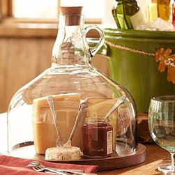 "Wine Jug Cloche Cheese Platter - Bring the tasting room to your party with this clever cloche. 13.25"" diameter, 13"" high Made of mango wood with a stained finish. Jug made of blown glass. Cork top."