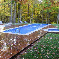 Endless Pools - Fastlane by Endless Pools - Playful fountains, a high-gloss deck, and a woodland setting make for a striking pool installation. The addition of a Fastlane, by Endless Pools, makes it ingeniously functional!