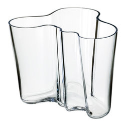 "iittala Aalto Clear Vase - 4-3/4"" - For nearly 80 years, the Savoy vase, designed by Finnish architect and furniture designer Alvar Aalto, has been one of the most famous pieces of glass in history. In 1936, Aalto anonymously entered his vase design for a competition at the Paris World's Fair. Aalto, Finnish for ""wave"" created an original glass vase with wavy lines and whimsical freeform design that to many suggests the undulating profile of a Finnish lake."