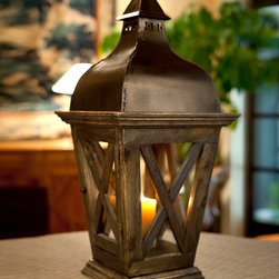 Lantern Wood, Iron, and Glass - Designed to turn the simplicity of a large pillar candle into a bold, classic statement of affection for old-world visual styles, the Lantern in Wood, Iron, and Glass carries the visual romance of a dark cobbled street, crafted in a form that sits beautifully on a garden table and makes a traditional romance of your holiday sideboard.  Dark patina enhances the depth.