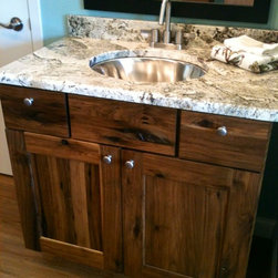 Showroom - Crazy Horse granite vanity top with under mount stainless sink. Danze Amalfi faucet. Woodland Cabinetry Rustic Portland Patina Hickory vanity.