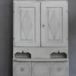 """Period Gustavian - Unusual Gustavian cabinet with integral clock, Sweden circa 1810. Certainly a rural interpretation of the popular urban pieces of the period, the upper cabinet doors have raised, reeded lozenges and interior shelves on either side of the chase for the clock pendulum and weights. The four lower drawers have raised circles with horizontal reeding. The clockworks are typical of those produced in Mora at the time, but the dial is signed """"Paris."""" Later base."""