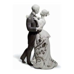 """Lladro Porcelain - Lladro Lovers Waltz Re Deco Figurine - Plus One Year Accidental Breakage Replace - """" The bride and groom take to the dance floor as family and friends look on with pent up emotion. The first notes strike up and the happy couple begin their first dance as man and wife. The Lladro Lovers Waltz Redeco 01007193 is inspired by one of the moments all married couples remember with special fondness, the music that accompanies them forever and is still capable of tugging at their heartstrings whenever they hear it.  The white porcelain in the bride�s dress contrasts with the gray porcelain of the groom�s suit.  The embroidery and details of her dress are depicted using platinum luster, whose glazed and matte finishes further enhance the ornamentation. Hand Made In Valencia Spain - Sculpted By: Virginia Gonzalez - Included with this sculpture is replacement insurance against accidental breakage. The replacement insurance is valid for one year from the date of purchase and covers 100% of the cost to replace this sculpture (shipping not included). However once the sculpture retires or is no longer being made, the breakage coverage ends as the piece can no longer be replaced. """""""