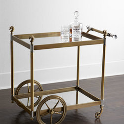 """Jonathan Adler - Jacques Bar Cart - BRASS - Jonathan AdlerJacques Bar CartDetailsBar cart crafted of brass with an antiqued finish.Polished-nickel and Lucite accents.Two mirrored glass shelves.Smooth-rolling wheel base.32.25""""W x 20""""D x 32""""T.Boxed weight approximately 68 lbs. Please note that this item may require additional delivery and processing charges.Designer About Jonathan Adler:Potter designer and author Jonathan Adler launched his first ceramics collection in 1994. His design philosophy: create a foundation of timelessly chic furniture and accessorize with abandon. With his roots still firmly in pottery he has expanded to become a complete lifestyle brand offering furniture lighting decorative objects fashion accessories and more. He is dedicated to bringing style craft and joy to life."""
