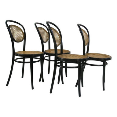 "Thonet - Pre-owned Michael Thonet A6658 Bentwood Side Chair - S/4 - These Michael Thonet designed bentwood side chairs are classics! The bentwood side chairs have the additional elegance of hand-woven cane in the seat and back. These chair's classic elegance makes them a great addition to a home, restaurant or office.    Original European Thonet factories in Radomsko Poland, and Brno, Czech Republic, using historic molds and techniques, manufactured these pieces. Remarkably few changes have been necessary over the last 150 years. The factories still follow the 18th century production methods developed by Michael Thonet to produce historically accurate, handsome, and sturdy bentwood chairs, stools, tables, and accessories. Cane seats are hand-tied, and wood laths steamed and bent into curved jigs then dried, sanded, and finally stained and varnished before being assembled.     They were featured in House Beautiful's design trend section: ""Everywhere We Look.""    Check the seller's other listings for a Thonet armchair in the same style.    Seat height 18 1/4""   Seat diameter 16 1/4"""