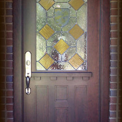 """Craftsman Doors - Here is a popular 36"""" x 80"""" Honduran Mahogany door is installed in a home in Auburn, Alabama.  It is shown with custom leaded seedy glass with amber diamonds and a hand painted and fired shield in the center.  The heavy ledge and dentil is reminicent of designs by Frank Loyd Wright.  The hardware is Rocky Mountain hand cast bronze."""