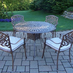 Oakland Living - 5-Pc Traditional Round Dinning Set - Includes capital table, four stackable chairs with cushions and metal hardware. Lattice pattern and scroll work. Handcast. Hardened powder coat. Fade, chip and crack resistant. Warranty: One year limited. Made from rust free cast aluminum. Antique bronze finish. Minimal assembly required. Table: 48 in. Dia. x 29 in. H. Chair: 23 in. W x 22 in. D x 35.5 in. H (25 lbs.)The Oakland Mississippi collection combines grace style and modern designs giving you a rich addition to any outdoor setting. We recommend that the products be covered to protect them when not in use. To preserve the beauty and finish of the metal products, we recommend applying an epoxy clear coat once a year. However, because of the nature of iron it will eventually rust when exposed to the elements.