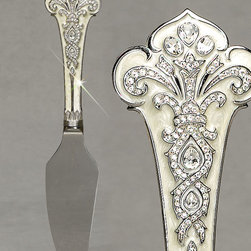 """Jay Strongwater - Cake Knife - Jay StrongwaterCake KnifeDetailsFrom the Duchess Collection.Handle white hand-painted enamel over metal in fleur-de-lis design; hand-set clear Swarovski crystals. Silver-tone trim.Blade engraved with """"Jay Strongwater."""" Approximately 11""""L x 2""""W x 0.75""""T.Hand wash. Handcrafted in USA.Designer About Jay Strongwater:Jay Strongwater's love of the elegant but vividly bejeweled objet whether it's meant to rest on a tabletop or the graceful curve of a woman's neck has led him on a journey through the worlds of fashion and home furnishings. He began his career while a student at the Rhode Island School of Design. After garnering raves for a necklace he'd made his mother he took jewelry samples to open buyer days at some of New York's finest department stores and soon a burgeoning business was born. At the age of 23 Strongwater met designer Oscar de la Renta with whom he began to collaborate on jewelry designs for runway shows. The move to home accessories was delightfully serendipitous & organic. For the 1994 holiday season Strongwater sent gifts of jewel-encrusted filigree picture frames to friends fashion editors and buyers who immediately fell in love with the design. By 1998 his Jewels for the Home collection had supplanted his fashion business. In essence Strongwater created his own niche: the jeweler turning his meticulous eye and art toward a world beyond a woman's wrists neck and ears."""