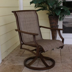 "Hospitality Rattan Chub Cay Sling Patio Swivel Rocking Dining Chair - Dark Bronz - Offering as much style as substance, the Hospitality Rattan Chub Cay Sling Patio Swivel Rocking Dining Chair - Dark Bronze is sure to quickly become your most favorite spot on the patio or by the poolside. Boasting a simple, yet elegant look that effortlessly blends classic style and contemporary aesthetics, this swivel rocking dining chair will grab attention in any setting. Boasting a tubular extruded bamboo-look aluminum frame in a unique powder coated dark bronze finish that will not rust, it features an exclusive, custom-made Twitchell sling fabric, which is so comfy that it eliminates the need for cushions. Plus, it swivels so you can stay up to speed with all the conversations around you, even as the gentle rocking motion seats you in luxurious comfort throughout your meal. Sturdily built to last for years, this weather- and UV-resistant swivel dining chair is stackable for convenient storage.About Hospitality RattanHospitality Rattan has been a leading manufacturer and distributor of contract quality rattan, wicker, and bamboo furnishings since 2000. The company's product lines have become dominant in the Casual Rattan, Wicker, and Outdoor Markets because of their quality construction, variety, and attractive design. Designed for buyers who appreciate upscale furniture with a tropical feel, Hospitality Rattan offers a range of indoor and outdoor collections featuring all-aluminum frames woven with Viro or Rehau synthetic wicker fiber that will not fade or crack when subjected to the elements. Hospitality Rattan furniture is manufactured to hospitality specifications and quality standards, which exceed the standards for residential use.Hospitality Rattan's Environmental CommitmentHospitality Rattan is continually looking for ways to limit the impact on the environment and is always trying to use the most environmentally friendly manufacturing techniques and materials possible. The company manufactures the highest quality furniture following sound and responsible environmental policies, with minimum impact on natural resources. Hospitality Rattan is also committed to achieving environmental best practices throughout its activity whenever this is practical and takes responsibility for the development and implementation of environmental best practices throughout all operations. Hospitality Rattan maintains a policy of continuous environmental improvement and therefore is a continuing work in progress.Hospitality Rattan's Environmentally Friendly Manufacturing ProcessAll of Hospitality Rattan products are green. From its basic raw materials of rattan poles, peels, leather, bamboo, abaca, lampacanay, wood, leather strips, and boards, down to other materials like nails, staples, water-based adhesives, finishes, stains, glazes and packing materials, all have minimum impact to the environment and are safe, biodegradable, recycled, and mostly recyclable. Aside from this, the products have undergone an environmentally-friendly process that makes them """"greener."""" The company's rattan components are sourced from sustained-yield managed forests, which means that the methods used to grow and harvest the rattan vines ensure the long-term life of the forest and protect the biodiversity of the forest's ecosystems.Hospitality Rattan is committed to buying and using all materials, from rattan and hardwood to finishing materials, from reputable and renewable suppliers and seeks appropriate evidence that suppliers are in compliance with this policy. Hospitality Rattan strives to use materials that are processed in an environmentally responsible manner, or consist of a high level of recycled material. Finishing materials and stains used in Hospitality Rattan's furniture products consist of 75% water-based solutions which evaporate upon application with reduced or Volatile Organic Compounds (VOCs). The furniture factories use water-based glues, stains, topcoats and other finishes on all of their products. The switch from traditional solvent-based processes to water-based processes involved consolidating several processes by the factories, resulting in an 85% reduction in VOC emissions."