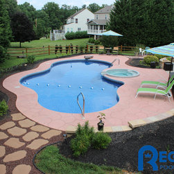 2012-2013 Pools & Spas - This 21' x 40' Freefrom-shaped pool features a spillover spa and dive rock. The pool deck connects nicely to an eating area and a fire pit.  This is located in Bel Air, Maryland in Harford County.