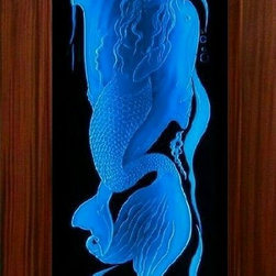 Wood door and LED enhanced carved glass - We just finished photographing this Sapele wood door I built for local artist Loren Schumann in Sarasota ,Florida using LED technology to enhance his beautiful carved glass. The photo shown is a sample of the many colors possible with these lights .The LED lights can be frozen on one color or allowed to transition from one to another..Besides the photos we also made a video of this process.