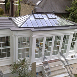 Rooftop view of Orangery - This photo shows exactly what distinguishes an orangery from a conservatory. The Orangery is the predecessor of the conservatory and is differentiated by the solid flat roof portion that surrounds the perimeter of the building allowing soffits on the interior. The soffits allow a convenient location for lights and A.C outlets. At the exterior above the soffits are sloped box gutters.