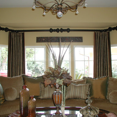 """Draperies - Stationary side panels with decorative accent fabric applied to side hems. The draperies are mounted on 3"""" wood poles with additional crests in the center of the poles and mitered to fit the angle of the bay."""