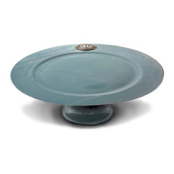 Coquille Cake Stand - Mist - The delicately luminous quality of the heirloom blue-grey glaze used for the Coquille Mist Cake Stand recalls the ephemeral coolness of sea-spray, an impression confirmed and made epicurean by the richly-detailed, stylized pewter shell embedded in the rim of this artisanal serving piece. Add a handsome, thoughtful quality to your table setting with this dramatic cake stand.