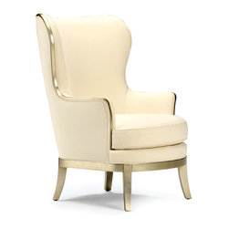 Veronica Chair - Smooth, graceful wingback lines flow into the form of the Veronica Chair, a beautiful upholstered armchair meant to adorn upscale living rooms, exquisite bedrooms, and dream-home libraries.  In a surprising touch of glamor that has all the more impact for its unexpected placement, silver leaf finishes the saber legs and the narrow wood trim that edges the neat tuxedo arms.