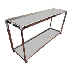 Pre-owned Italian Chrome & Smoked Glass Console Bar Cart - Such a versatile piece! Chrome and smoked glass bar cart in an uncommon size and shape--would also work as a buffet, console table, entry/hall table or vanity. Quite sturdy, heavy construction with gorgeous waterfall edges. Impeccable Italian quality craftsmanship! Designer unknown.    Currently has castors to function as a bar cart or rolling buffet, but if you would prefer to use as a console table, castors could be removed and replaced with feet.    Chrome and glass are both in excellent vintage condition with only minor wear consistent with age and use--nothing visible in use. All castors are in very good condition and roll smoothly. Showroom ready!    Please note: Seller has the matching smaller bar cart or cocktail/side table for sale in a separate listing!