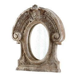 Inglewood Mirror - The cameo proportions of the oval Inglewood Mirror are given weight and wonder by the driftwood-colored frame whose heavily carved ornamentation circles the pane.  With the mirror set deep within, the frame is prominent and combats crisp geometry with a top-heavy, abstracted array of floral motifs and architectural volutes below a draped arch.