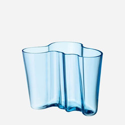 "iittala - 6.25"" Alvar Aalto Vase in Light Blue - The undulating forms of the objects in the Aalto collection are like the Finnish landscape with its thousands of lakes - beautiful, alive and untamed. Glassblowers at the Iittala factory still meticulously handcraft the legendary vases that are variations on one theme, fluid organic shapes that let the end user decide the use. Interpretations of the shape in new colors and materials add to the growing Alvar Aalto Collection and remain true to his original design idea. Features: -Organic form. -Height: 6.25""."