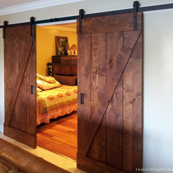 Barn Door Installations - Barn Door Kit in Rustic Alder with Classic Flat Track in Oil Rubbed Bronze. A great choice for this bedroom!