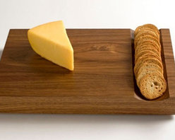PHASE DESIGN - Cheese Board by Phase Design - Crafted out of a solid slab of walnut, Phase Design's signature wood, this dual purpose cheese and cutting board is an updated take on traditional party serve ware. The groove in the wood creates the perfect space to place a line crackers or a cut baguette. The scoop can act as a handy channel to push freshly chopped vegetables or herbs when this doubles as a cutting board.