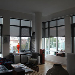 Charles In Willaimsburg Has Solar Shades - Charles was looking for a way to limit both heat and glare in his Williamsburg apartment. To accomplish this, he chose solar shades for his living room and office/guest bedroom in Linux Black 14048. For a sleek industrial look, Charles opted for no valence, loop control and a fabric wrapped bottom bar.