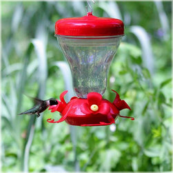 Perky Pet - Magnolia Hummingbird Feeder Multicolor - 120TF - Shop for Feeders from Hayneedle.com! The Magnolia Hummingbird Feeder is just what you need to attract hummingbirds to your garden. The wide-mouth top and the top-fill design makes refilling the feeder a breeze while four red magnolia-shaped feeding ports ensure that the little hummingbirds can easily enjoy the nectar. A convenient patented Push-Pull technology facilitates effortless refilling - just push pour then pull and lock - it's that easy! Cleaning the Magnolia Hummingbird Feeder is simple too because it is designed with fewer parts than other feeders. The durable clear plastic construction makes it easy to monitor nectar levels in this 16-ounce hummingbird feeder. Feeder Hanging TipsHummingbird feeders should be hung out of direct sunlight away from windy areas and out of reach of cats. You may also want to place the feeder in and around flowers. This will help attract more hummingbirds to your feeder. Ideally a sheltered location with south-eastern exposure is best for hanging bird feeders because birds like to feed in the sun and out of the wind. Birds also prefer not to have any obstructions over their feeding area so they can see any predators. Feeder CareKeeping your feeder clean and full of fresh nectar is very important to the health of visiting hummingbirds. It is recommended that you clean your hummingbird feeder every week. A mild soap and water solution can be used for cleaning. However if additional cleaning is needed you can use diluted vinegar. It is not recommended that you put any bird feeders into your dishwasher for cleaning. About WoodstreamA privately-held company with a long-standing positive reputation Woodstream is a global manufacturer and marketer of quality products from pets and wildlife control and home and garden products to bird feeders and garden decor. They have a 150-year history of excellence growth and innovation and have built a strong presence in key markets thro