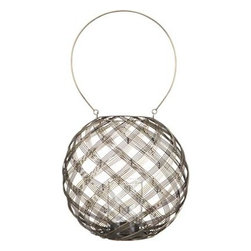 Hadley Brass Lantern - Loose weave of iron strands spins an open orb around a clear glass cylinder to flicker candlelight indoors or out, on a tabletop or hung by its hoop handle. Antique brass finish burnishes the glow of small pillar candle. Especially festive grouped in multiples in the home, patio or garden. Open orb spun in an almost plaid weave, from slim iron wires