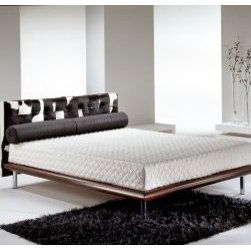 Italydesign Studios - Mies Bed Pony Skin - Our Mies bed is a completely new design that embodies the minimalist appeal of the International Style. Inspired by the famous Mies Van der Rohe Day Bed, this platform bed features a distinctive tufted headboard cushion covered in sophisticated natural haired cow hide. The black and white hides are hand cut into individual squares and sewn together using the capitonne technique with black leather piping over each seam. Leather covered buttons enhance the deep tufting. Lean back and enjoy the comfortable padding while reading or watching television.The thick, rounded, solid wood frame in a walnut stain is supported by tubular chromed steel legs. Plastic inserts inside the leg tips protect floors. Flexible beechwood slats eliminate the need for a bulky box spring and allow air to circulate beneath the mattress.The natural hide is very durable and easy to clean - just vacuum and wipe with a damp, sudsy terry cloth. The striking originality of this bed is further enhanced by the natural variation of the hides ensuring each bed is a one-of-a-kind creation.With its architectural spare lines and timeless appeal, the Mies Bed will enhance both modern and traditional interiors. Stocked to fit three American mattress sizes: Queen, California King, and Eastern King. Designed by and available exclusively from italydesign.com. Made in Italy. Also available with a solid black, smooth leather headboard cushion.Compliment this bed with the Focus Dresser, Focus Tallboy and the Focus Nightstand. Pricing by request. Please call 510-420-0383 or email info@italydesign.com.