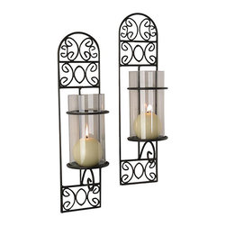 Danya B - Madeira Iron Wall Sconces (Set of 2) - This set of two black iron wall sconces adds light and style to any room. With a distinctive scrollwork design and the included glass votive candleholders, you can enjoy a candlelit evening anytime you choose.