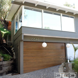 Modern Garage Doors With Sloping Bottom Sections for Uneven Garage Floors - Converting a carport into a real garage can be architecturally challenging and even more so when the ground is uneven. Retrofitting a sloped ground garage opening with a functional and aesthetically pleasing garage door can be daunting and for a lot of semi-custom garage door companies--impossible! At Dynamic Garage Door we thrive on the impossible and we simply don't put any stops to real custom garage door projects.