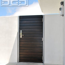 Dynamic Garage Door - Custom Crafted Modern Side Gate in a Horizontal Slat Design With Chrome Hardware - Linear horizontal design is often used in Modern architecture to accentuate the swift flowing lines of modernistic elegance. This custom wood entry gate with its horizontal v-goove style slats is minimalistic with an encrusted chrome lever handle that shimmers modern elegance as you approach to open the gate.