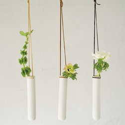 Hanging Test Tube Vase by Pigeon Toe Ceramic - These beautiful hanging test tube vases are made from porcelain and suspended by leather lace. I think they would be lovely hung over a table or in front of a window.