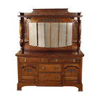 Antiques - Antique English Solid Walnut Mirrorback Sideboard Buffet Server - Country of Origin: England Circa: 1899 Solid Walnut Construction Elegant Crown Large Beveled Mirror 2 Beautiful Turnings 2 Small Shelves 4 Drawers Dovetail Joinery Attractive Handles 2 Carved Cabinet Doors Lock Mechanism 2 Keys Present 4 Shelves (2 Removable) Stunning Condition Top Quality Strong & SturdyThis is a gorgeous antique English solid walnut mirrorback sideboard buffet server. It has a lovely beveled cornice on top with a display shelf which has attractive dental molding on its front and sides and it features a large beveled and scalloped mirror which is in very good condition. This mirror is beautifully decorated with rich carvings of foliage, scroll-like and other elegant designs on its top and sides, and it also has two convenient small shelves with a fluted stand and beautiful turnings. The top surface is in very good condition and it has a very nice finish even though it has a minor age appropriate wood separation on its center and other superficial marks which are not distracting at all.This sideboard has four smooth operating drawers that are well constructed with dovetail joinery and they have attractive round handles. One of the drawers sticks out a bit when it is closed but as seen on the pictures it is barely noticeable and can be repaired if necessary. There are two cabinets with four shelves, two which are removable. The cabinet doors have beautiful carved decorations of foliage designs with attractive raised beveled surfaces. Both doors have a lock mechanism with two keys present but only one of their locks functions properly. Overall this server is in very good cosmetic and structural condition for its age, circa 1899, and it is strong and sturdy. This is a gorgeous piece of furniture that will not only enrich your home decor with its presence but will also become a treasured heirloom in your family! It is of top quality and its condition is absolutely stunning!