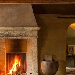 Fireplaces out of Reclaimed Antique Stone (Mediterranean Style) - This is a simple hand carved picture frame Bolection stone fireplace mantle installed with antique herringbone terracotta brick size tiles, Brought to you by our carvers at Ancient Surfaces.