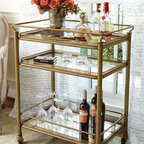 Burgundy Bar Cart - Our designers fell in love with a centuries old antique brass cart they found in Marseilles. Reinterpreted here, crafted in the Empire style, with three smoked mirror shelves, our Burgundy Bar Cart has antiqued brass finished legs, rails and delicate filigree surrounds. Smooth-rolling casters (accompanied by a brake should you need it) keep things moving in style.