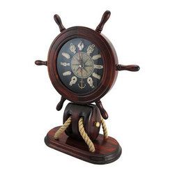 Wooden Ship`s Wheel and Nautical Knots Mantel Clock - This beautiful mantel clock is a wonderful addition to the home of sailing enthusiasts, and complements nautical decor. It features a wooden ship`s wheel and measures 13 1/4 inches tall, 11 inches long, and 4 3/4 inches wide. The 5 1/4 inch diameter clock face has nautical knots to mark the hours, as well as Roman numerals, and has a mariner`s compass in the center. The clock features quartz movement and runs on 1 AA battery (not included). This piece is an eye-catching accent in your home or office, and makes a great gift for a friend.