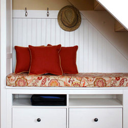 """Storage Bench Cushions - Customer Photo: """"Space is at a premium in our small, vacation cabin, so I created a built-in seating/storage area under the stairway in the living room to utilize that unused space more efficiently and provide extra seating. Cushion Source made the boxed edge, 3"""" thick custom bench cushion from my template with Sunbrella Splendor Fiesta with matching cording, and the three 13"""" square, knife-edge throw pillows with Sunbrella Spectrum Grenadine with contrasting cording in Sunbrella Dupione Cornsilk. The formerly uninspired space has been transformed into a charming, country nook. The custom cushions and pillows were the finishing touch. Thank you Cushion Source!"""""""