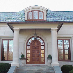 Front Door - Traditional entry door features raised panels and arched transom.